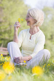 Woman sitting outdoors smiling and holding a Buttercup flower — Stock Photo