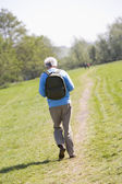 Man walking outdoors with in background — Stock Photo
