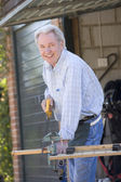 Man at shed sawing wood and smiling — Stock Photo