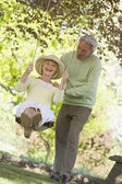 Couple outdoors with tree swing smiling — Stock Photo