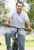 Hombre en bicicleta al aire libre sonriendo — Foto de Stock