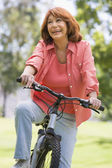Woman on bike outdoors smiling — Stock Photo