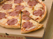 Pepperoni Pizza in a Take Away Box with a Cut Slice — Stock Photo