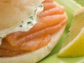 Ahumada bagel de salmón y crema de queso con una rodaja de limón — Foto de Stock