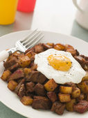 Corned Beef Hash With a Fried Egg and Black Pepper — Stock Photo