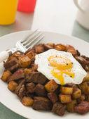 Hash de carne enlatada com um ovo frito quebrado e pimenta preta — Foto Stock