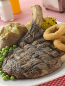Ribeye Steak on the bone with Baked Potato Peas Onion Rings and — Stock Photo