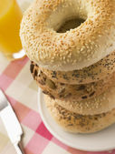 Stack of Seeded Bagels with a Glass of Orange Juice — Stock Photo