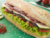 Deli Sub Sandwich on a Chopping Board — Stock Photo