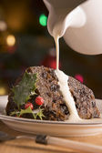Portion of Christmas Pudding with Pouring Cream — Stock Photo