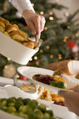 Serving Roast Potatoes at Christmas Lunch — Stock Photo