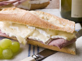 Brie and Ham Baguette with White Wine and Grapes — Stock Photo