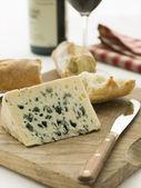 Cuña de queso roquefort con baguette rústica y vino tinto — Foto de Stock