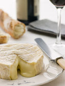 Round of camembert cheese with French stick and Red Wine — Stock Photo