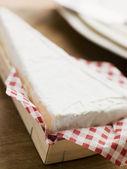 Cuña de queso brie en una caja de madera — Foto de Stock