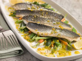 Fillets of Sea bass with Baby Vegetables and Saffron Butter — Stock Photo