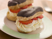 Chocolate and Strawberry filled eclairs — Stock Photo