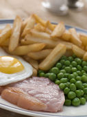 Gammon steak fried egg erbsen und chips — Stockfoto