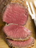 Roast Topside of British Beef carved on a Chopping Board — Stock Photo