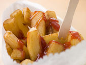Chip Shop Chips in a Bag with a Wooden Fork and Tomato ketchup — Stock Photo