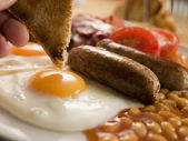 Dipping Toast into a Fried Egg on a Full English Breakfast — Stock Photo