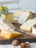 Selection of British Cheeses with Walnuts Biscuits and Grapes — Stock Photo