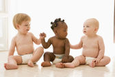 Three babies sitting indoors holding hands — Stock Photo