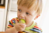 Young boy eating apple indoors — Stock Photo