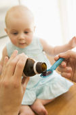 Mother giving baby medicine indoors — Stockfoto