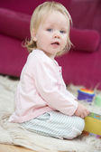 Baby in living room with toys and book — Stock Photo