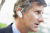 Businessman wearing earpiece outdoors — Stock Photo