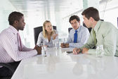 Four businesspeople in a boardroom talking — Stock Photo