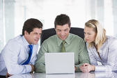 Three businesspeople in a boardroom looking at laptop — Stock Photo