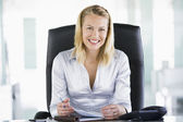 Businesswoman in office with personal organizer smiling — Stock Photo