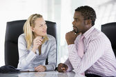 Two businesspeople in office talking — Stock Photo