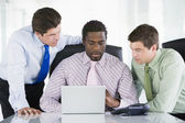 Three businessmen in a boardroom looking at laptop — Stock Photo