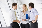 Three businesspeople standing in corridor talking and smiling — Stock Photo
