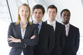Four businesspeople standing in corridor smiling — Stock Photo