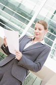 Businesswoman standing outdoors reading paperwork — Stock Photo
