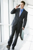 Businessman walking in corridor using cellular phone — Stock Photo