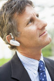 Businessman wearing headset outdoors — Stock Photo