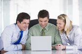 Three businesspeople in office with laptop smiling — Stock Photo