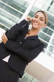 Businesswoman standing outdoors on cellular phone smiling — Stok fotoğraf