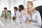 Four businesspeople in boardroom with one businesswoman yawning — Stock Photo