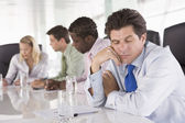 Four businesspeople in boardroom with one businessman sleeping — Stock Photo