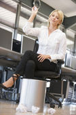 Businesswoman in office space throwing garbage in bin — Stok fotoğraf