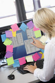 Businesswoman in office pointing at monitor with notes on it — Stock Photo