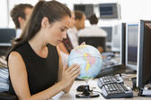 Businesswoman in office space with desk globe — 图库照片