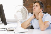 Businessman in office with computer and fan cooling off — Fotografia Stock