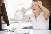 Businesswoman in office with computer and fan cooling off — Fotografia Stock